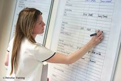 Woman writing information on a whiteboard
